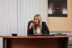 礼服的恼怒的妇女呼喊在电话的 库存图片