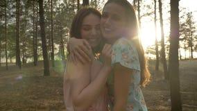 礼服的拥抱在森林的,笑两个年轻白种人女孩,无所事事,看照相机,在的自然 影视素材