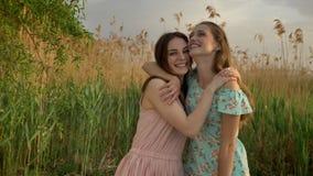 礼服的拥抱在森林的,笑两个年轻白种人女孩,无所事事,自然在背景中,看 股票视频