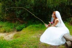 礼服的新娘有坐由湖的钓鱼竿的设法捉住她的一个新郎 免版税库存图片