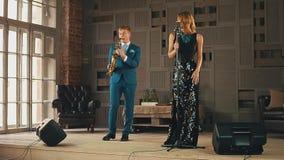 礼服的爵士乐蓝色衣服的歌唱者和萨克斯管吹奏者在阶段执行 高雅 股票视频