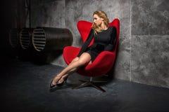 黑礼服的白肤金发的女孩坐红色扶手椅子 免版税库存图片