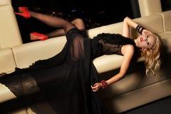 黑礼服的白肤金发的妇女 免版税库存照片