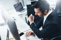礼服的确信的人认为和与台式计算机一起使用在现代lightful办公室 水平 蠢材 免版税库存照片