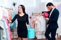 礼服的美丽的女孩和衣服的一个可爱的人购物 他们在一个轻的陈列室里 免版税图库摄影