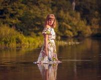 礼服的美丽的女孩在河 免版税库存照片