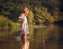 礼服的美丽的女孩在河 免版税库存图片