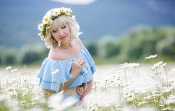 礼服的美丽的女孩在雏菊花田 库存图片