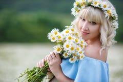 礼服的美丽的女孩在雏菊花田 免版税库存图片