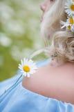 礼服的美丽的女孩在雏菊花田 免版税图库摄影