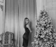 黑礼服的美丽的女孩自圣诞前夕一,黑白色 免版税库存图片