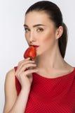 礼服的美丽的女孩 与完善的裸体构成的画象 查看照相机 吃红色草莓 健康的食物 隔绝在丝毫 免版税库存图片