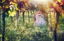 礼服的美丽的女性在葡萄园里 库存照片