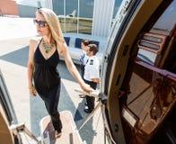 礼服的美丽的妇女上私人喷气式飞机的 免版税库存照片