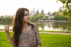 礼服的美丽的妇女在河背景特写镜头画象 免版税库存照片