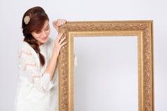 礼服的美丽的妇女拿着大镀金面框架 免版税库存照片