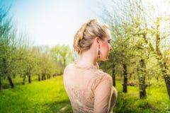 礼服的美丽的少妇作公园的 库存图片