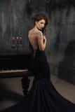 黑礼服的美丽的少妇在与大烛台蜡烛和酒,城堡的黑暗的剧烈的大气的一架钢琴旁边 Boh 免版税库存照片