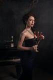黑礼服的美丽的少妇在与大烛台蜡烛和酒,城堡的黑暗的剧烈的大气的一架钢琴旁边 Boh 免版税图库摄影