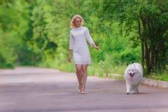 礼服的美丽的年轻白肤金发的女孩走与一条白色蓬松狗的在夏天庭院里 库存照片
