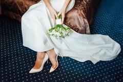 礼服的美丽的新娘在白色鞋子投入 图库摄影