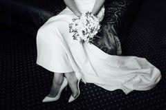 礼服的美丽的新娘在白色鞋子投入 库存图片