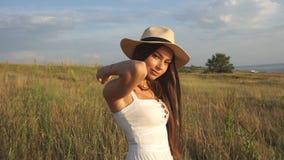 礼服的美丽的深色的女孩在帽子 在摆在的草中的妇女在领域微笑和 夏天休息和放松在自然 股票录像