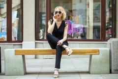 黑礼服的美丽的白肤金发的女孩坐在summe的一条长凳 库存照片