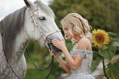礼服的美丽的白肤金发的女孩抚摸在自然的一匹灰色马  免版税图库摄影