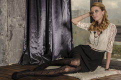 礼服的美丽的白肤金发的妇女在一间古色古香的屋子坐由窗口 库存图片