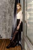 礼服的美丽的白肤金发的妇女在一间古色古香的屋子坐由窗口 库存照片