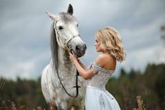 礼服的美丽的苗条白肤金发的女孩看灰色马,在n 免版税库存照片