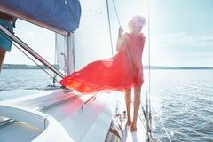 礼服的美丽的年轻性感的深色的女孩和构成、夏天旅行在一条游艇有白色风帆的在海或海洋海湾的 免版税图库摄影