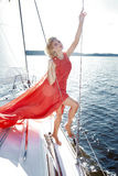 礼服的美丽的年轻性感的深色的女孩和构成、夏天旅行在一条游艇有白色风帆的在海或海洋海湾的 免版税库存照片