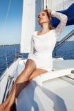 礼服的美丽的年轻性感的深色的女孩和构成、夏天旅行在一条游艇有白色风帆的在海或海洋海湾的 库存图片