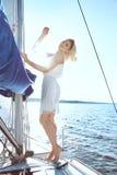 礼服的美丽的年轻性感的深色的女孩和构成、夏天旅行在一条游艇有白色风帆的在海或海洋海湾的 图库摄影