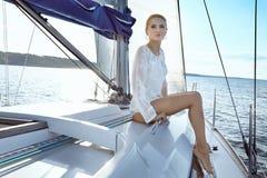 礼服的美丽的年轻性感的深色的女孩和构成、夏天旅行在一条游艇有白色风帆的在海或海洋海湾的 免版税库存图片
