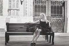 黑礼服的美丽的年轻时髦的白肤金发的妇女坐a 图库摄影