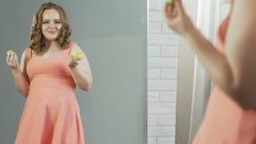 礼服的超重女性吃油炸圈饼的,当敬佩她的在镜子时的反射 股票录像