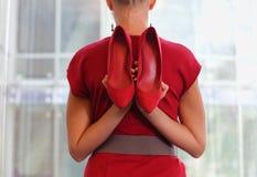 礼服的适合的女商人有两只红色高跟鞋的 免版税图库摄影