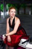 礼服的骑自行车的人女孩在的一辆摩托车 免版税库存照片