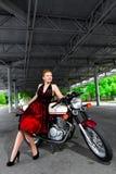 礼服的骑自行车的人女孩在的一辆摩托车 库存图片