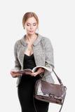 黑礼服的,夹克美丽的女商人金发碧眼的女人读杂志的在灰色背景 免版税库存照片