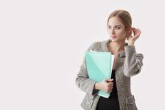黑礼服的,拿着纸文件夹和微笑在灰色背景的夹克年轻美丽的女商人 库存图片