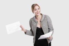 黑礼服的,拿着纸文件夹和微笑在灰色背景的夹克年轻美丽的女商人 免版税图库摄影