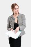 黑礼服的,拿着纸文件夹和微笑在灰色背景的夹克年轻美丽的女商人 库存照片