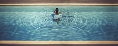 礼服的年轻女性在水池 免版税库存图片