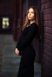 黑礼服的年轻时尚妇女在砖墙 免版税库存照片