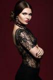黑礼服的年轻美丽的妇女在marsala颜色背景 免版税库存照片