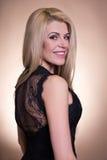 黑礼服的年轻美丽的白肤金发的妇女在灰棕色 免版税库存照片